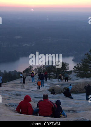 Worshipers watch as the sun rises during the Easter Sunrise Service on the top of Stone Mountain, Ga. The world's - Stock Photo