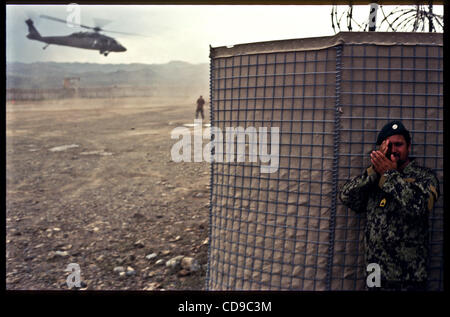 Jul 01, 2010 - Paktika, Afghanistan - An Afghan National Army soldiers shields his face as a U.S. Army UH-60 Black - Stock Photo