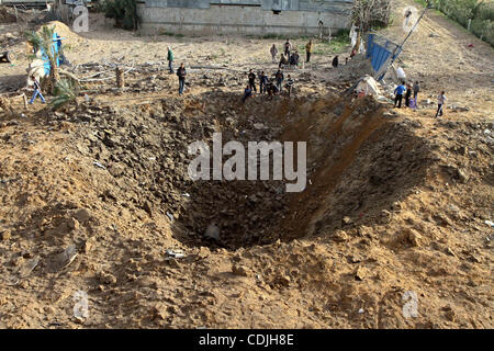 Palestinians stand next to a crater left after a missile fired from an Israeli warplane hit Nusairat refugee camp, - Stock Photo