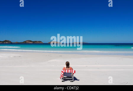 Mar 26, 2011 - Esperance, Western Australia, Australia - A beachgoer sits on the white sand beach of Lucky Bay in - Stock Photo