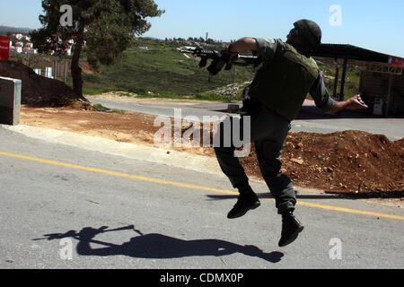 Apr 15, 2011 - Ramallah, West Bank, Palestinian Territory - An Israeli soldier hurls tear gas canister toward Palestinian - Stock Photo