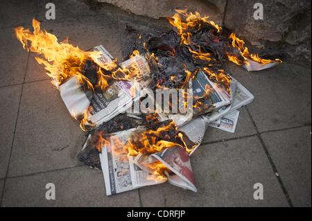 July 10, 2011 - London, England, UK - A protestor burns copies of The News of the World outside the News International - Stock Photo