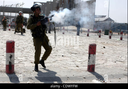 An Israeli soldier fires tear gas canister during clashes with Palestinian protesters at the Qalandia checkpoint - Stock Photo