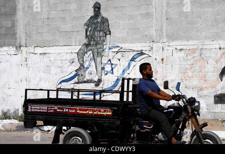 Sep. 28, 2011 - Gaza City, West Bank - Palestinians ride motorcycle past a graffiti depicting a Palestinian militant - Stock Photo