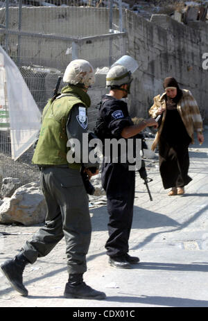 A Palestinian woman walks past Israeli soldiers standing guard in the east Jerusalem neighborhood of Silwan, Thursday, Sept. 29, 2011. Israel on Tuesday approved construction of 1,100 homes for Jews on the annexed land in the West Bank, a move that could complicate international efforts to renew pea Stock Photo