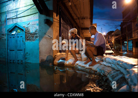Oct. 28, 2011 - Bangkok, Bangkok, Thailand - Two men catch fish in the residential area flooded by high tide of - Stock Photo