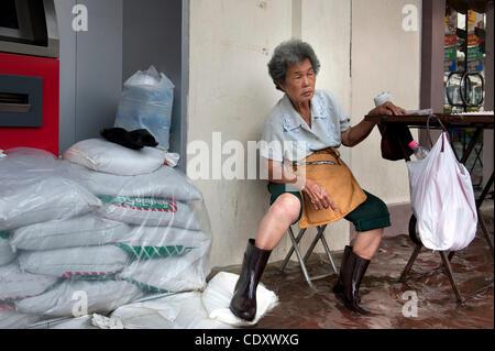Oct. 31, 2011 - Bangkok, Bangkok, Thailand - A woman sells lottery ticket amid inundated street in Chinatown, Bangkok..Thai - Stock Photo