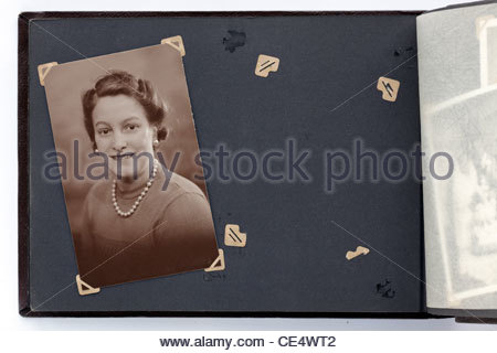 a 1930s portrait and a missing picture on a vintage photo album page - Stock Photo