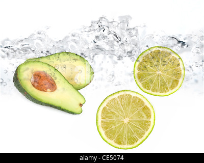 Green limes and avocado in water dropped isolated on a white - Stock Photo