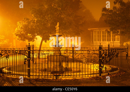 Late night fog descends on the Jubilee fountain and bandstand in Royal Avenue Gardens, Dartmouth, Devon, UK - Stock Photo