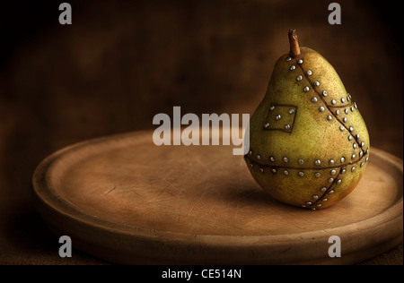 pear manipulated fruit with nails holding it together concept for genetic manipulation - Stock Photo