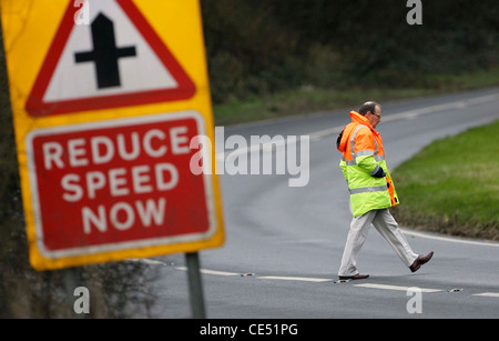 A road traffic investigator measures an area of road were a fatal Road Traffic Accident occurred. Picture by James - Stock Photo