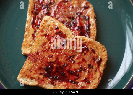 Open face peanut butter and jam whole wheat toast on a green plate - Stock Photo