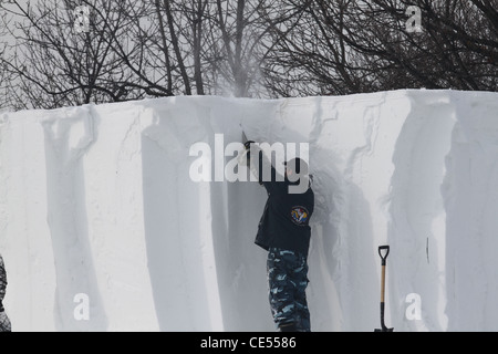 Man snow sculptor working with a power tool. - Stock Photo