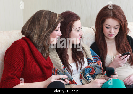 Three generation z teenage girl friends aged 15 years looking at photos on a mobile phone whilst sitting on a sofa - Stock Photo