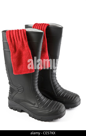 One pair of red socks inside a pair of black rubber safety wellington boots isolated on a white background. UK - Stock Photo