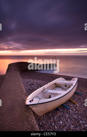 Fishing boat on Sidmouth beach at dawn, Sidmouth, Devon, England. Winter (January) 2012. - Stock Photo