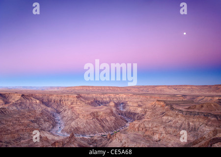 Full moon setting over the Fish River Canyon in southern Namibia at dawn. - Stock Photo