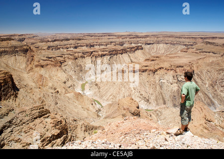 A man stands looking out across the Fish River Canyon in southern Namibia. - Stock Photo