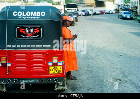 Worker of Sri Lankan traditional taxi(tuk-tuk) waiting for clients. - Stock Photo