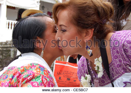 Two mexican women greeting each other in mexico city mexico stock two mexican women greeting each other in street one indigenous woman sunny day with polite kiss m4hsunfo