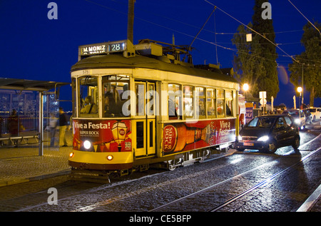 Portugal, Lisbon.  Tram 28 passing by a cafe in the Alfama on it's way to Martim Moniz. - Stock Photo