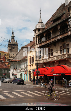 Europe, Romania, Sighisoara, Lower Town street around medieval citadel with the Clock Tower in the background - Stock Photo