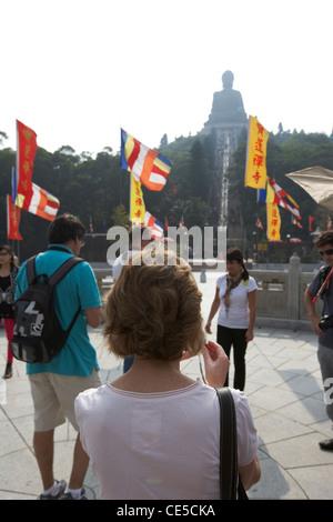 female caucasian tourist taking photos at Di Tan in front of the tian tan big buddha in haze of smog ngong ping - Stock Photo