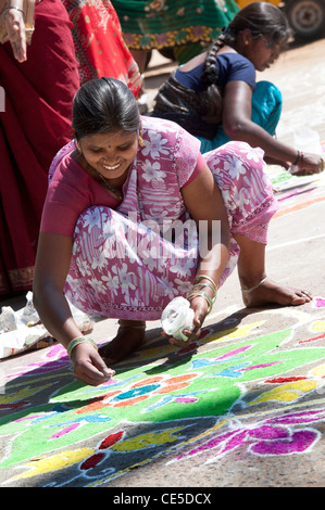 India women making Rangoli festival designs in an Indian village competition. Puttaparthi, Andhra Pradesh, India - Stock Photo
