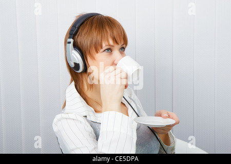 The girl in headphones with a microphone drinks coffee - Stock Photo