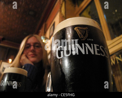 Beautiful blonde lady pictured with a fresh pint of Guinness - Stock Photo