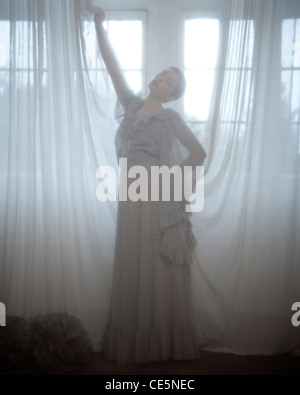 young girl behind curtains a woman wearing a long grey dress standing behind a voile curtain stock photo