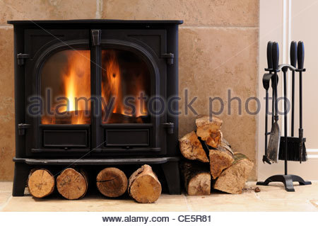 Firewood and wood burner in a living room in Dorset, England. Digitally altered to remove makers name from wood - Stock Photo