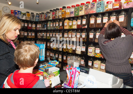 A small boy buying sweets with his mum in a Uk sweetshop - Stock Photo