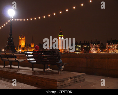 Tourists sit on a bencj on London's South Bank and take in a view of the Houses of Parliament illuminated at night. - Stock Photo