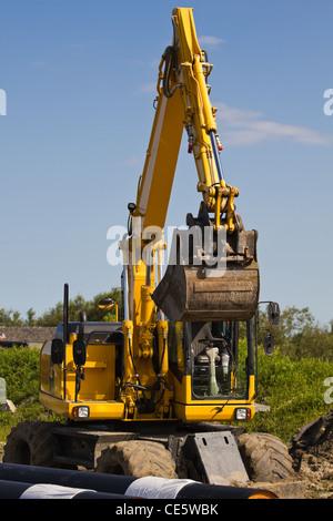 Excavator at work digging up ground - Stock Photo