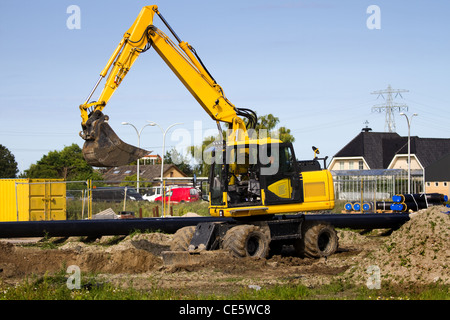 Excavator at work digging up ground for new to build houses - horizontal - Stock Photo