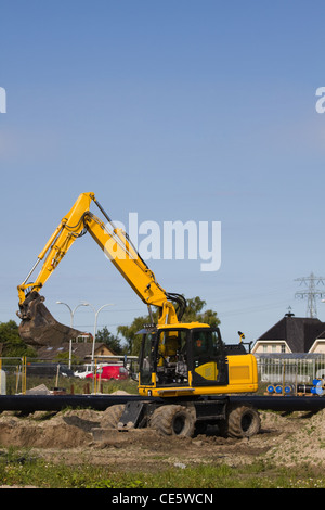 Excavator at work digging up ground for new to build houses - vertical - Stock Photo
