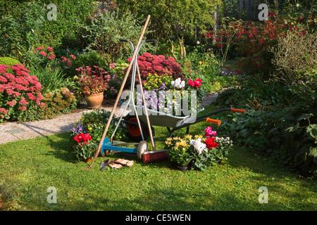 Wheelbarrow, grass mower, garden equipment, preparing for planting new plants in the garden on early September morning - Stock Photo
