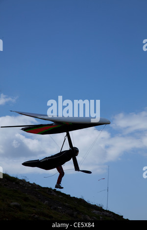 Hang glider launching from hillside on Col Rodella, in Dolomite Alps Italy, Europe. - Stock Photo