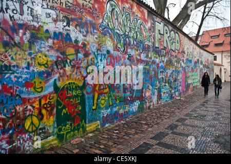 people walking in front of the John Lennon tribute wall in the Mala Strana district of Prague, Czech Republic - Stock Photo