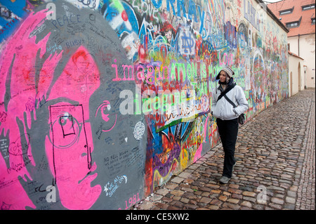 Tourist at the John Lennon tribute wall in the Mala Strana district of Prague, Czech Republic - Stock Photo
