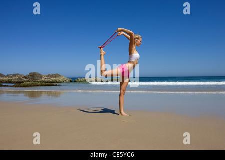 Girl exercising on the beach - Stock Photo