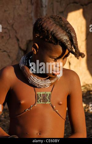 Himba girl with braided hair in village near Opuwo, Namibia - Stock Photo