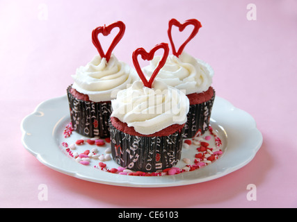 Red Velvet cupcakes with cream cheese frosting, decorated for Valentine's Day. - Stock Photo