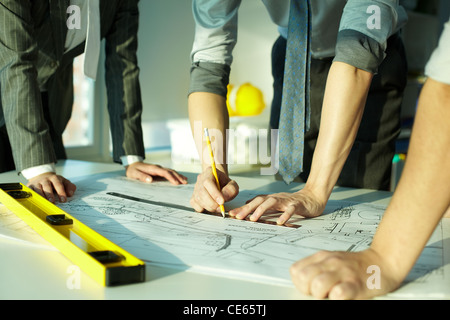 Three pairs of hands sketching a housing project - Stock Photo