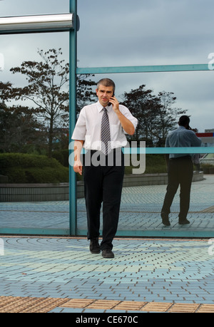 Businessman using a mobile phone while is walking in front of some blue corporate building windows. - Stock Photo