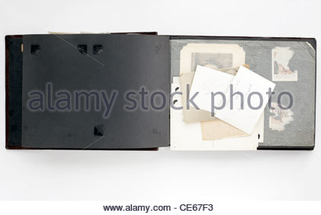 open old photo album with images loose on the page - Stock Photo
