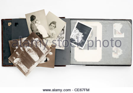 family photo album with loose images from 1920s and 1950s - Stock Photo