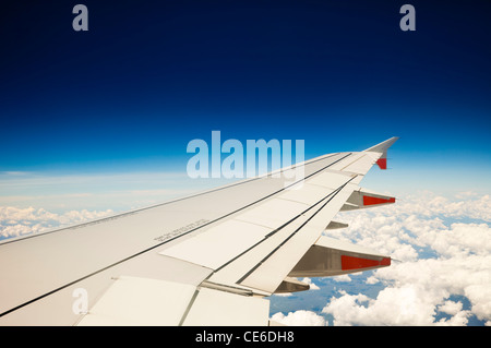 View of jet aircraft wing above the clouds. - Stock Photo